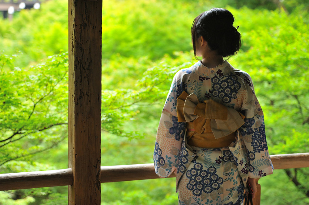 Back of a woman wearing a kimono with the obi sash tied in the tateya musubi style of kimono